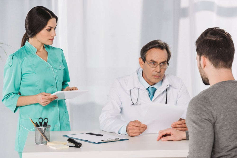 male doctor and female nurse talking to male patient