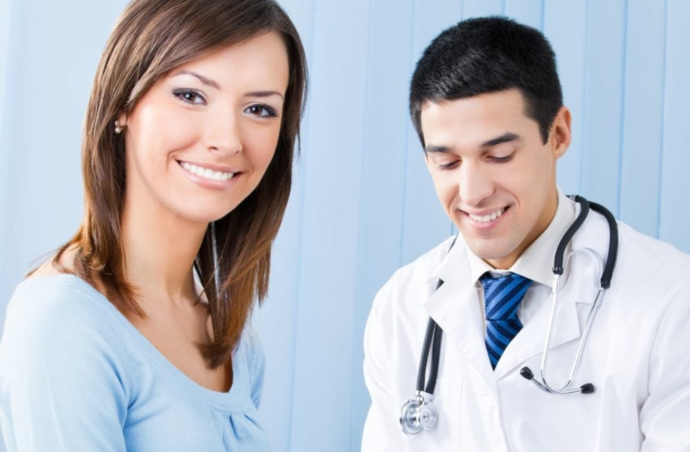 Portrait of happy smiling female patient and doctor at office. Focus on woman.